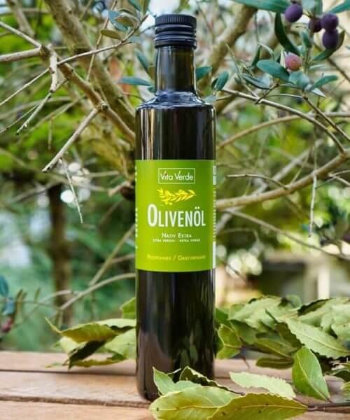 Bio Olivenöl Vita Verde auf Holzkiste vor Olivenbaum. Koroneiki Oliven