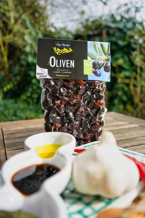 Vita Verde Bio Oliven Classic im Beutel verpackt mit Öl und Balsamico auf dem Holztisch